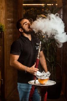 Молодой человек курит кальян с апельсином