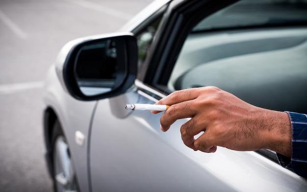 若い男が車の中でタバコを吸う