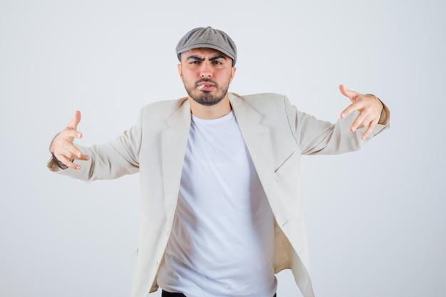 Giovane che fuma sigarette e allunga le mani in avanti in maglietta bianca, giacca e berretto grigio e sembra arrabbiato