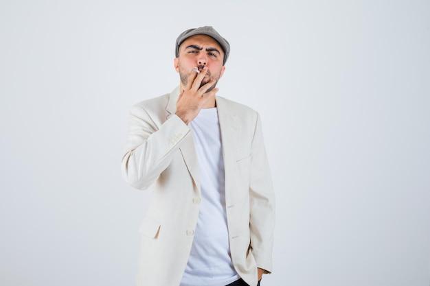Giovane che fuma sigarette in maglietta bianca, giacca e berretto grigio e sembra serio