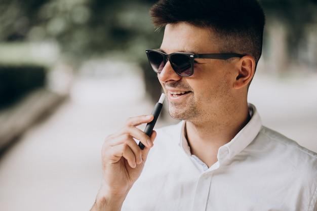 若い男が公園で外電気タバコを吸って