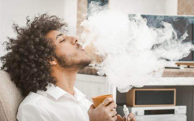 Курение молодого человека электронной сигареты дома. курильщик выдыхает большое облако дыма