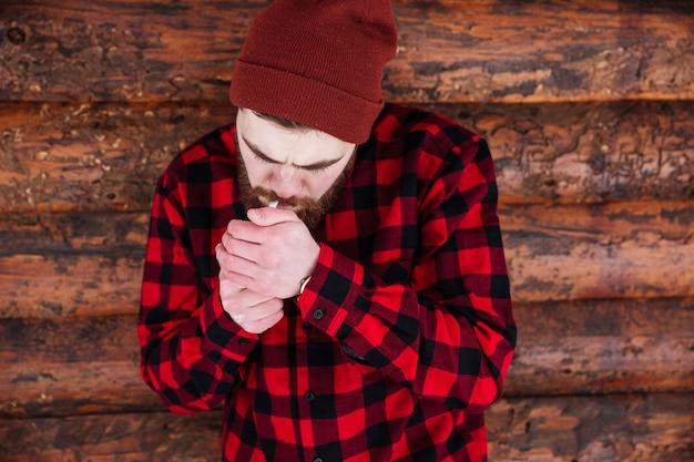 Молодой человек курит на деревянном доме