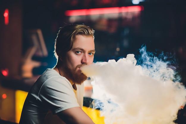 Young man smoking shisha at arabic restaurant - man exhaling smoke inhaling from a hookah.