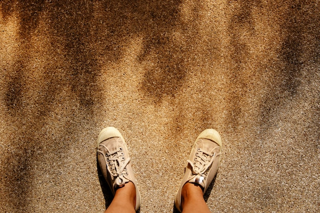 A young man in sneakers shoes standing against the hot sunlight.