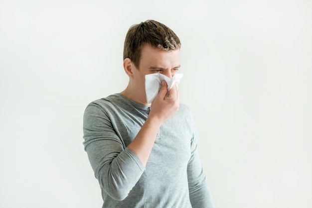Young man sneezing in handkerchief blowing wiping running nose, respiratory contagious symptoms , flu and coronavirus symptoms
