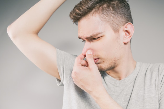 Young man sniffing an armpit