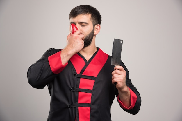 Young man sniffing a red pepper and holding knife.