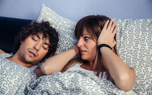 いびきをかく若い男と彼の妻は騒音に悩まされて彼女の耳を覆っている