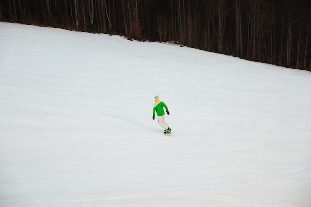 Young man snowboarder on the slopes frosty winter day