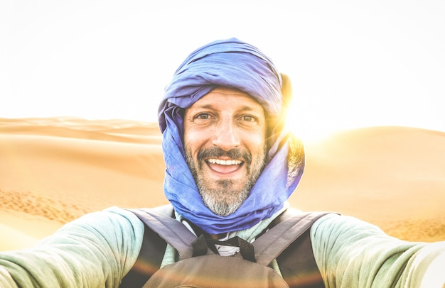 Young man solo traveler taking selfie at erg chebbi desert dune near merzouga in morocco