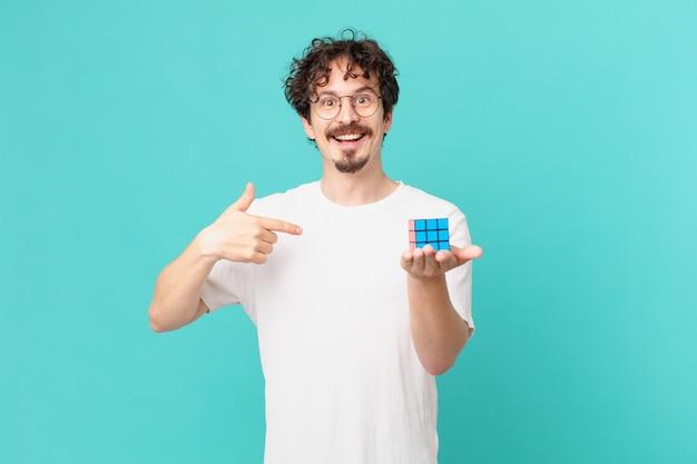 지능 문제를 해결하는 젊은 남자는 행복하고 흥분된 상태로 자신을 가리키고 있습니다.