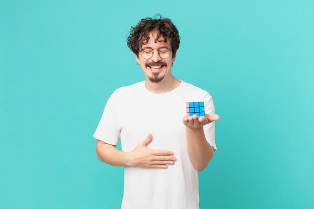 지능 문제를 해결하는 젊은 남자는 재미있는 농담에 큰 소리로 웃습니다.