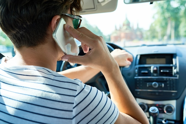 Young man speaking by phone in car