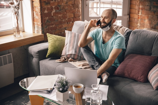 검역 및 프리랜서 작업을 하는 동안 집에서 전화로 말하는 청년
