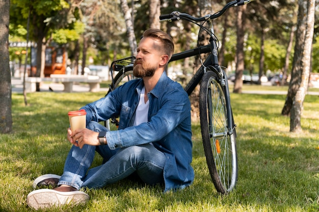 Young man spending time outside with his bike