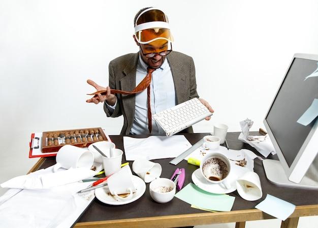 若い男が働いて目を覚まそうとしているときにキーボードに飲み物をこぼした