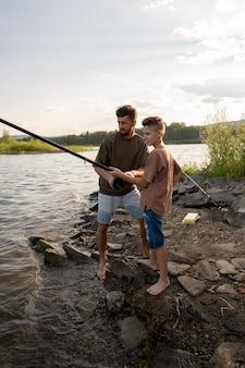 그의 아들과 함께 낚시하는 동안 막대에 물레를 돌리는 젊은 남자
