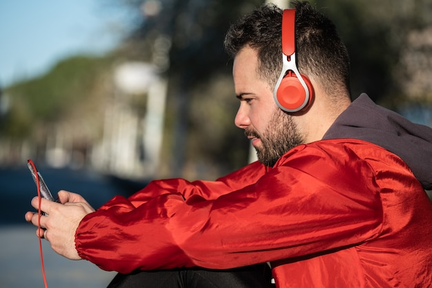 Young man in sportswear listening to music with a pair of headphones