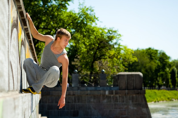 Young man in sportswear practicing parkour outside on stone wall on clear summer day