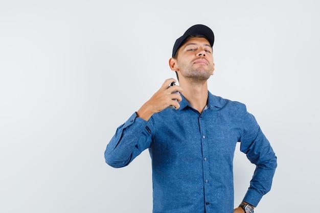 Молодой человек распыляет духи на себя в синей рубашке, кепке и выглядит элегантно, вид спереди.