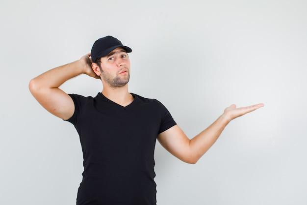 Giovane uomo diffusione palmo da parte con la mano dietro la testa in maglietta nera