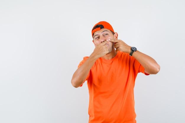 Молодой человек сжимает прыщ на щеке в оранжевой футболке и кепке