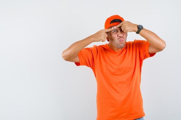 Молодой человек сжимает прыщ на лбу в оранжевой футболке и кепке, вид спереди.