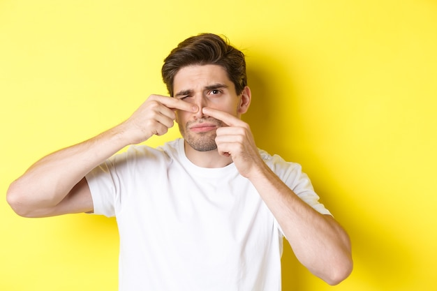 Young man squeezing pimple on nose, standing over yellow wall
