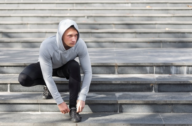 Young man on stairs tying his laces