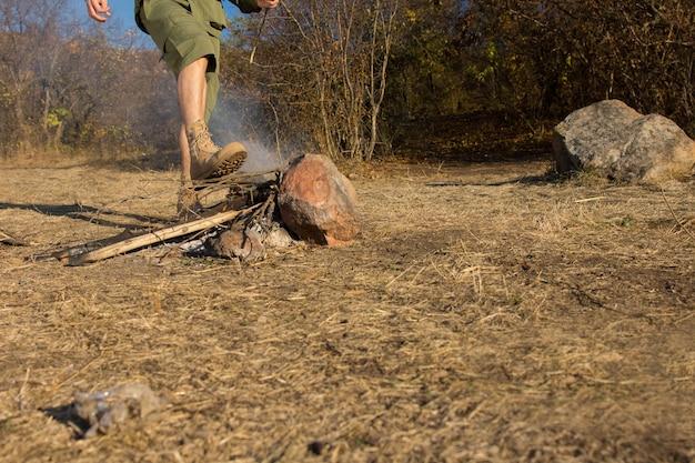 젊은 남자는 복사공간, 다리의 낮은 각도 보기와 함께 확산 위험을 피하기 위해 부츠를 신은 발로 캠프장에서 연기가 나는 불씨를 끄집어냅니다.