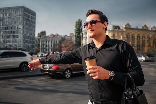 若い男は外に立ち、一杯の飲み物を保持します。彼は手を握る。男はタクシーに乗ろうとします。
