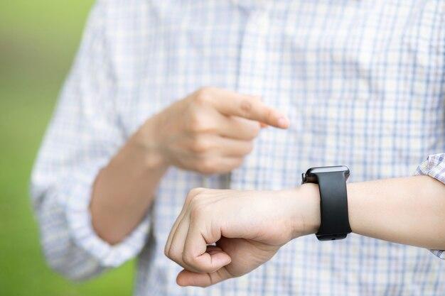 젊은 남자 스탠드 대기 시계를보고 타이머를 기대합니다. 회의는 시간 제한 개념 내에서 약속을 잡습니다. 손목 시계
