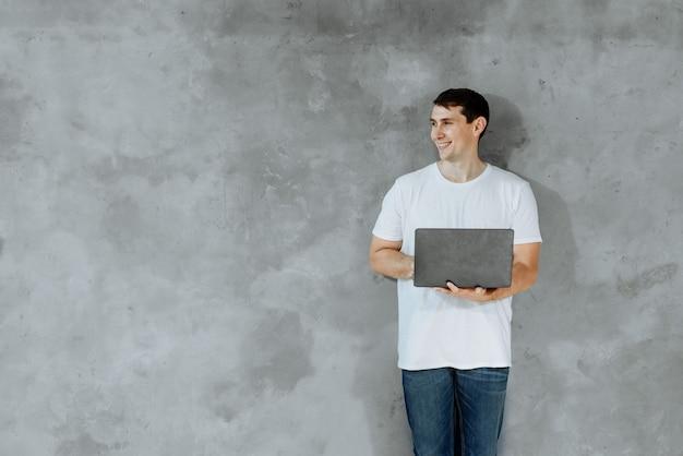 젊은 남자가 서서 회색 배경에 측면을 찾고 노트북 컴퓨터를 들고