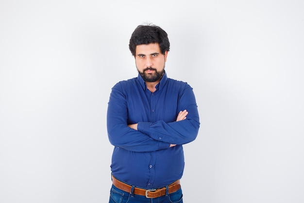 Молодой человек стоял скрестив руки в голубой рубашке и джинсах и выглядел серьезно. передний план.