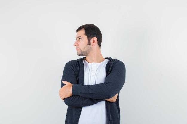 젊은 남자 서있는 팔은 흰색 티셔츠와 지퍼 앞 검은 까마귀로 넘어 진지하게 보입니다. 전면보기.