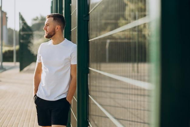 朝のスタジアムに立っている若い男