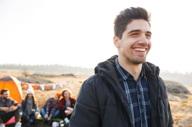 彼の友人とキャンプ場に立っている若い男