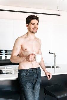 Молодой человек, стоя на кухне в помещении, пить кофе