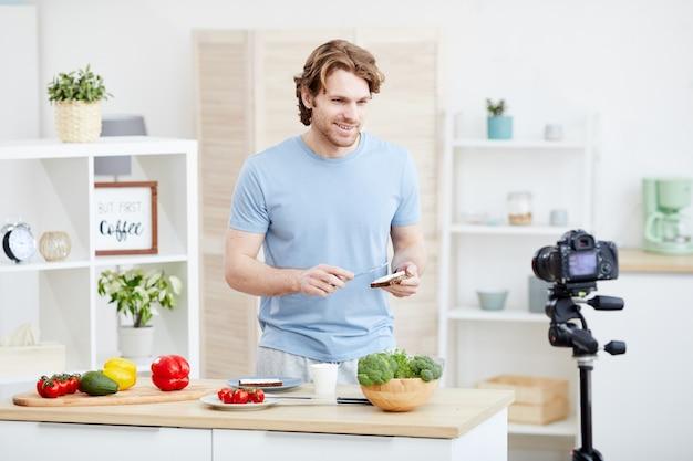 Молодой человек стоит за столом и готовит бутерброды и снимает видео для своего блога на кухне