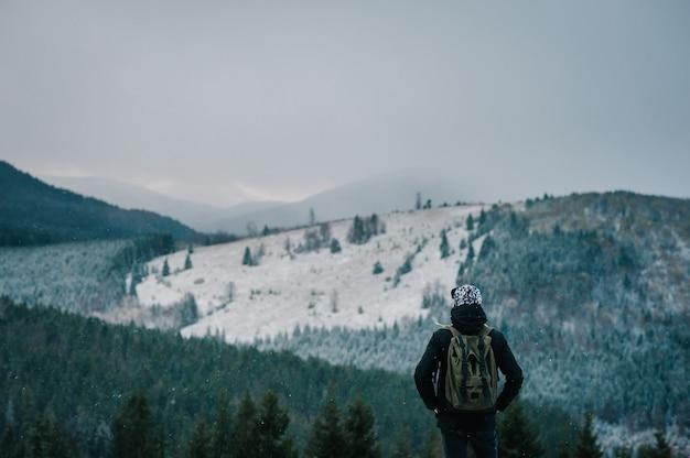 겨울 눈 덮인 산에서 절벽 꼭대기에 서서, 자연의 경치를 즐기는 젊은 남자.