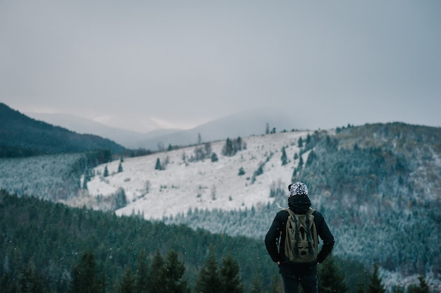 Young man standing back on top of cliff in winter snowy mountains, enjoying view of nature.