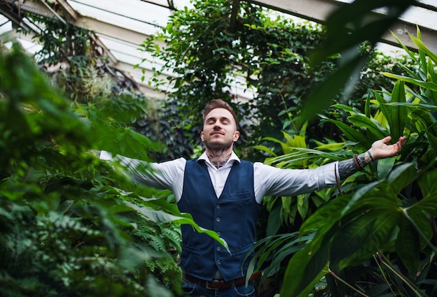 Young man standing in botanical garden, arms stretched. green bussiness concept.