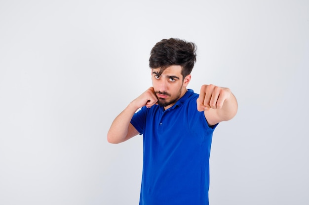 Giovane che sta nella posa del pugile in maglietta blu e sembra serio