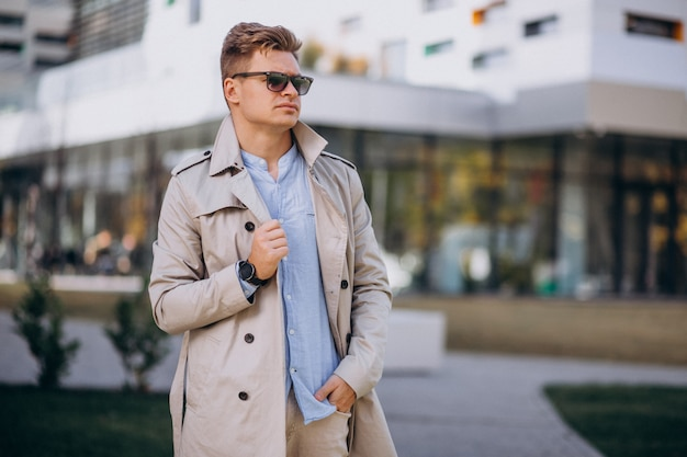 Young man standing by the business building