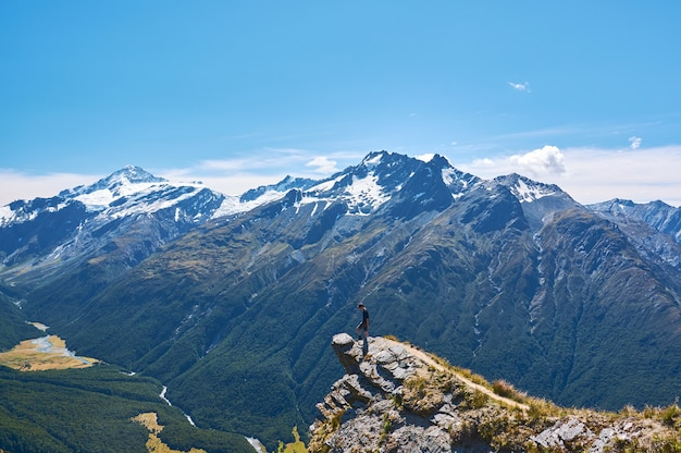 Young man standing on a cliff looking over the valley in new zealand