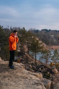 Un giovane uomo in piedi sul bordo di una scogliera Foto Gratuite