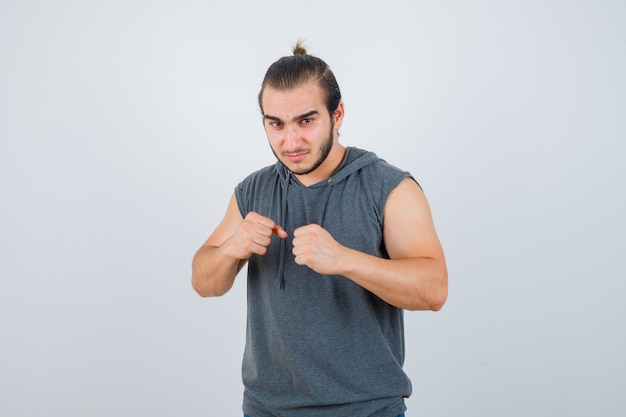 Young man standing in fight pose in sleeveless hoodie and looking confident. front view.