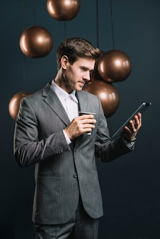 Young man standing in front of streamlined mirror round copper chandelier looking at digital tablet
