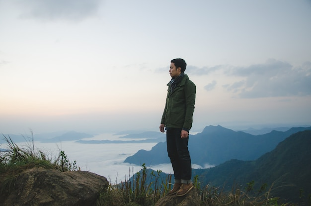 Young man standing on hill is wearing green coat